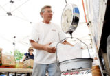 Alan Mazzotti weighs out vegetables for waiting customers at the Mazzotti's Farm booth at the...