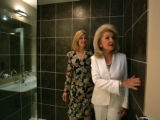 Realtor Diane Huttner (r) show client Debi Tepper the shower stall with ceramic tile at the...