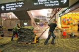 Mike Hart (cq), left, and Rahn Richards (cq) cart away some old carpet in the main terminal at...