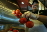 Chef Jose Santos holds some of the vine ripened tomatoes for their fresh salsa at Qdoba in Denver,...