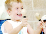 Andrew Vroman, 4, of Littleton smiles as he plays with the African drumming concert group, Istari,...