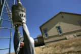 Joaquin Lopez (cq) lifts up a bucket of cement next to a new houses at the Anthem development in...
