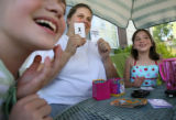 MJM087  Elisabeth Narcy (cq), 9, left, laughs as she plays a card game with neighbor, Ruth Rudd...