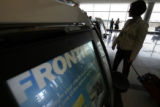 (009)  People wait at the check in at the Frontier Airlines counter at the Denver International...