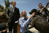 (047)  Dan Paul, center, of the Humane Society of the United States gets some love from a...
