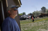 (474) David Herhager looks on from the backyard of his Westminster home property workers go on...