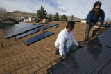 DM0077  Trester Dyke, left, and Randy Gonser with Akeena Solar install solar panels on the roof of...