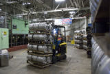 A forklift operator moves kegs of beer under a banner in an area which wil soon produce Coors  at...