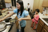 L-R-  Sabitra,  Som and Sabina,8, Baral prepare lunch in their Aurora apartment before Sol leaves...