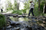 James Lester Armstrong, 64, of Denver, right, crosses a stream while hiking along a trail near...