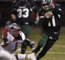 Pine Creeek High School quarterback Josh Chance (#11) right, ran past  Heritage High School...