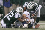 0360 Denver Broncos FB Peyton Hillis (22) is tackled by New York Jets cornerback Ty Law (22),...