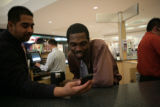 Mike Dominguez (cq) shows something on his phone to Vonzel Sawyer (cq) the group worked with Tatum...