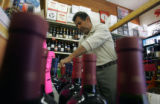 (PHOTO/ DENNIS SCHROEDER/ ROCKY MOUNTAIN NEWS) Sam Naoum stocks his shelves at his Liquor store in...