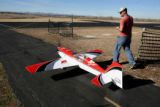 Cody Wilson (cq )brings his Comp ARF Extra 300 model airplane to the runway, Monday afternoon,...