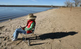 Laurel Miller (cq), Englewood, reads a book along waters edge, Monday afternoon, November 17,...