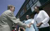 Mayor John Hickenlooper shakes hands with Shawna McCarther (cq), 20, a formerly homeless youth, in...