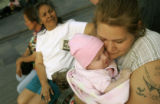 Leticia Guzman (cq), 22, right, cuddles with her baby, Sage Athena Guzman (cq), 3 months, on a...