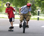 L to R: Spencer Wahl (cq),10, rides  a skateboard while being pulled by his fast peddling brother...