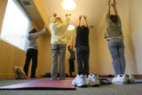 Marissa Manriquez (cq), center, leads a group of residents in a stretch class at a SPAN shelter,...