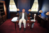 Rep. Tom Tancredo sits on the desk in his Capitol Hill office after his belonging were boxed up,...