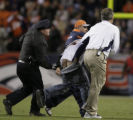 JPM1473 Denver Broncos security and Denver police escort a man who ran onto the field in fourth...
