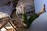 Sarah Schleper does her early-morning exercise routine in the bedroom as her husband, Federico...