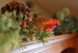 A glass holiday finch, made by Old World Christmas, jazzes up some simple garland above the...