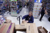 LIz Tibwell (cq), and employee at this Wallmart in Stapleton gets ready to stock some newly...
