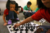 MJM072  Jasmine Jimenez (cq), 6, left, plays chess with her sister, Natalie Jimenez (cq), 7,...