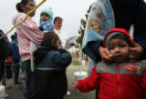(PG3310) Jesus Ortiz, 2, has his hood pulled over his head to keep warm while waiting in line on...