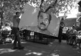 Artist Miguel Flores, right, and his friend, Jonathan Saiz remove a portrait of Saddam Hussein...