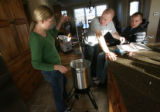 MJM077  Tracy Keil works on assembling a deep fry cooker, as her brother in law, Aaron Keil (cq),...