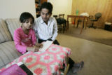 Som Baral, a 30 year old refugee from Bhatan, helps his daughter Sabina, 8 with her math homework...