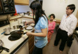 L-R-  Sabitra, Sabina, 8, and Som Baral prepare lunch in their Aurora apartment before Som leaves...