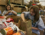 Volunteers, Jaimie Kirk, (cq), left and friend Brianna Morehead (cq) help unload donations,...