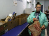 Julie Fischer (cq) picks out some bread, while waiting for her turn to pick up other food,...