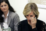 Charlotte Garrett (rt) wipes away tears at a press conference about her late husband Jeff...