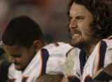 JPM871 Denver Broncos Ben Hamilton grimaces as he sits with Ryan Harris on the bench in the third...