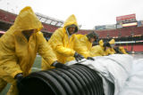 0155 Workers remove a tarp from the field as rain is forecasted throughout the game between the...