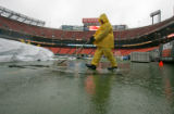 0180 Workers remove a tarp from the field as rain is forecasted throughout the game between the...