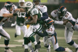 0420 New York Jets wide receiver Jerricho Cotchery (89) is surrounded by the Broncos defense in...