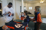 NFL Rookie of the Year candidate Eddie Royal (cq) autographs Bronco's merchandise, as he prepares...