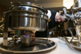 John Vargas lights the flame under a steam pot at a saute station in the Augusta room at The...