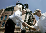 Sculptor, George Lundeen, cq, left, gives Colorado Rockies Chair and Chief Executive, Charles...