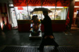 (0184) A man walks in the rain past Ben's Chili Bowl, a renowned hang-out of civil rights leaders...