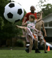 Leah Flores, 9, kicks an oversized soccer ball in Argo Park during a celebration during the...