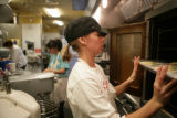 Delaney Sentes, 25, (cq) slides a tray into the oven while working at Indulge Bakery 1377 Forest...