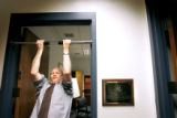 State Treasurer Mike Coffman does pull-ups in the doorway to his office Friday. Coffman put in his...