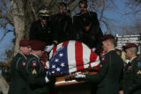 Military personal unload the casket of Justin Bauer (cq) during his gravesite service, Tuesday,...